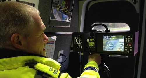 a police constable in high visibility jacket looks at a camera screen showing motorists