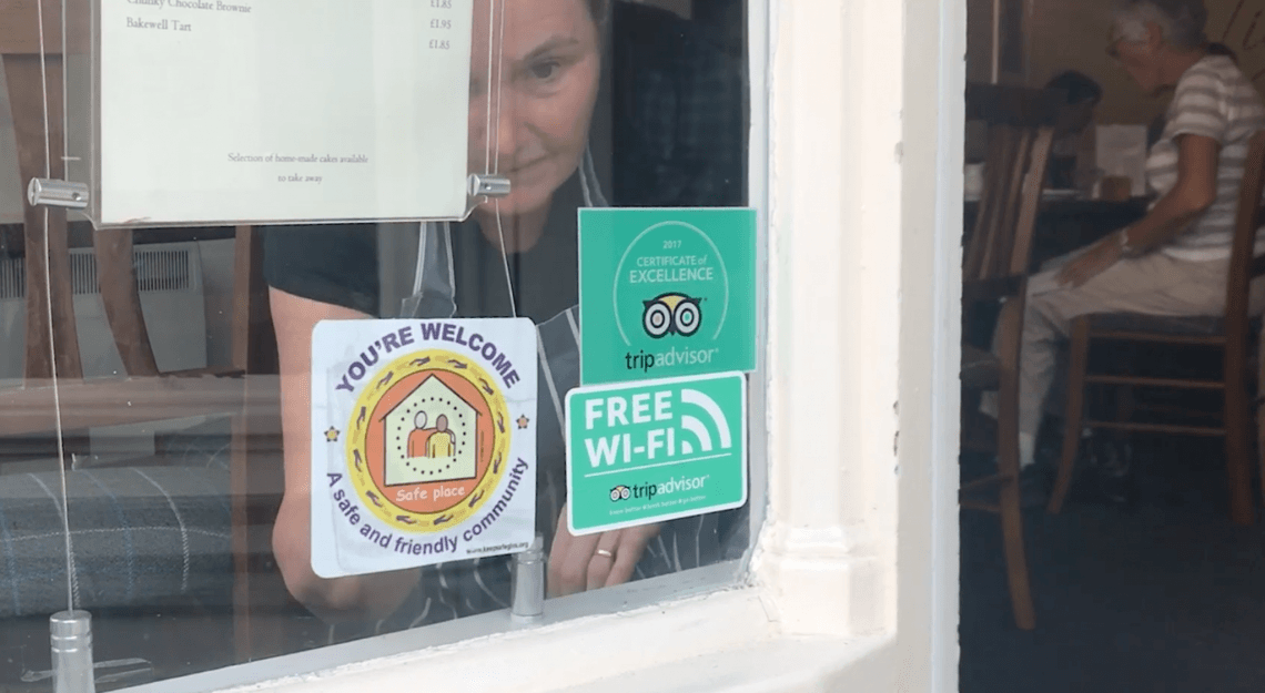 A woman puts up a sticker in a cafe window