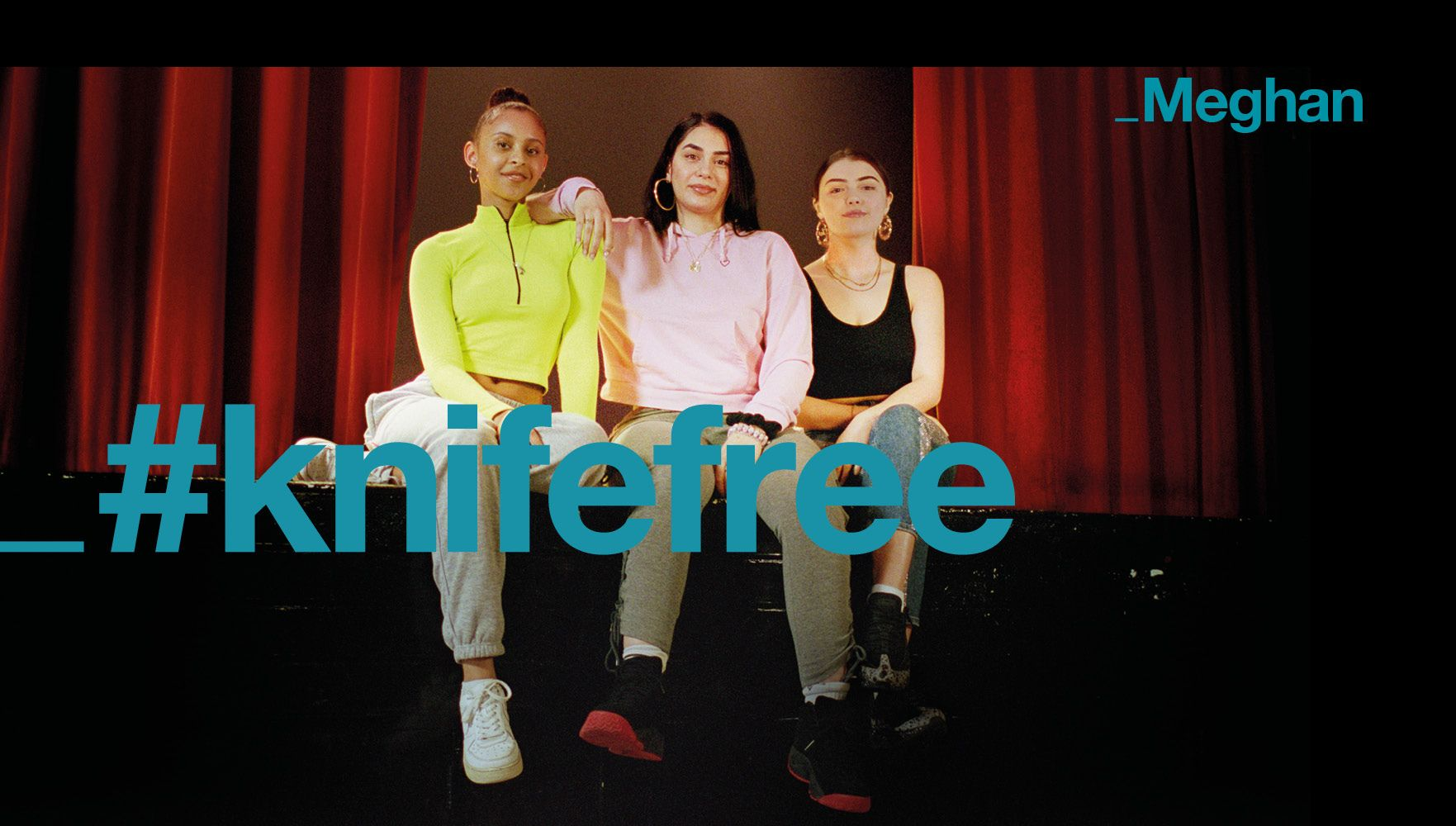 three young women sit on the edge of a stage with '#knifefree' superimposed on the image in turquoise lettering