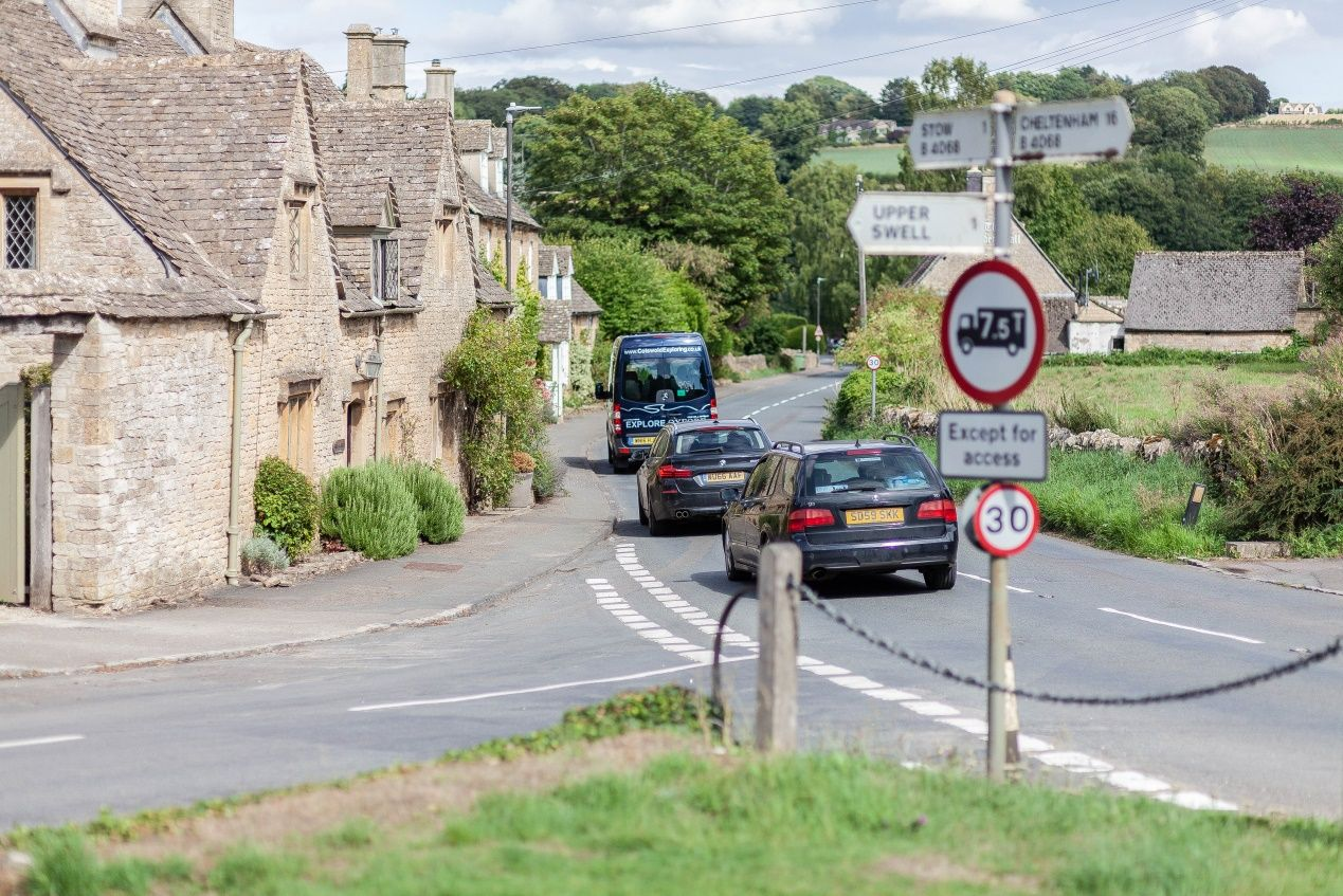 Cars driving through a sleepy Cotswold village in Gloucestershire