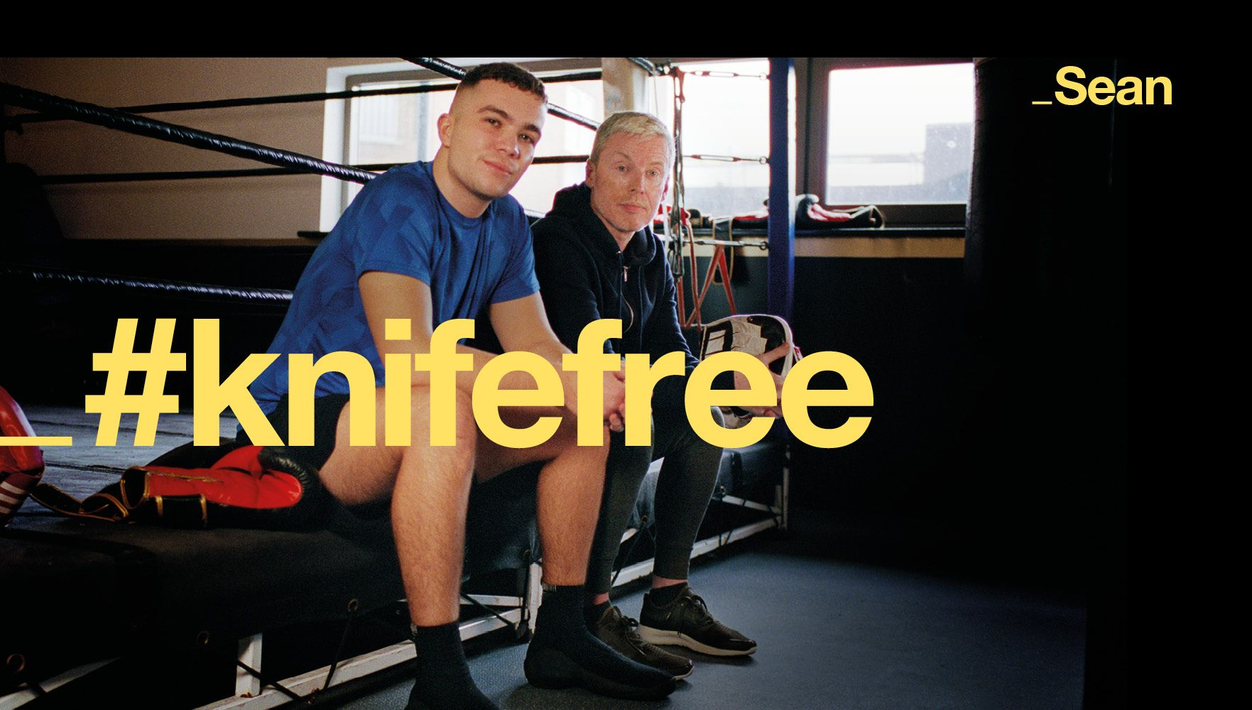 two men from anti knife crime campaign sit on the edge of a boxing ring with #knifefree superimposed on top