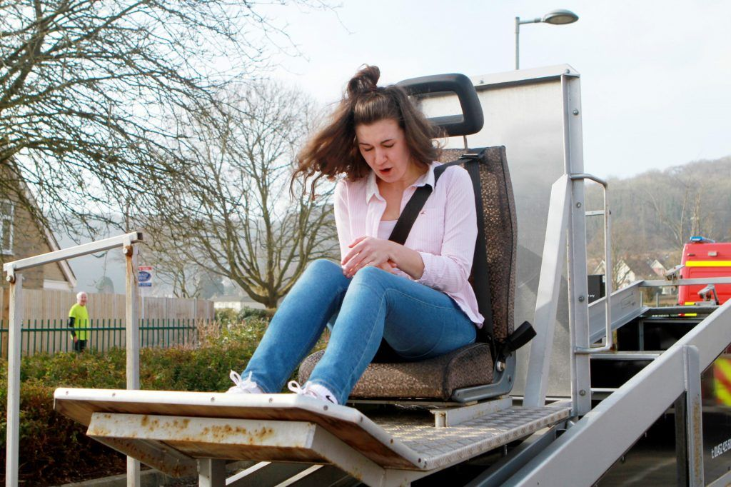 a young woman sits in a mechanical contraption that mimics the impact of a car crash