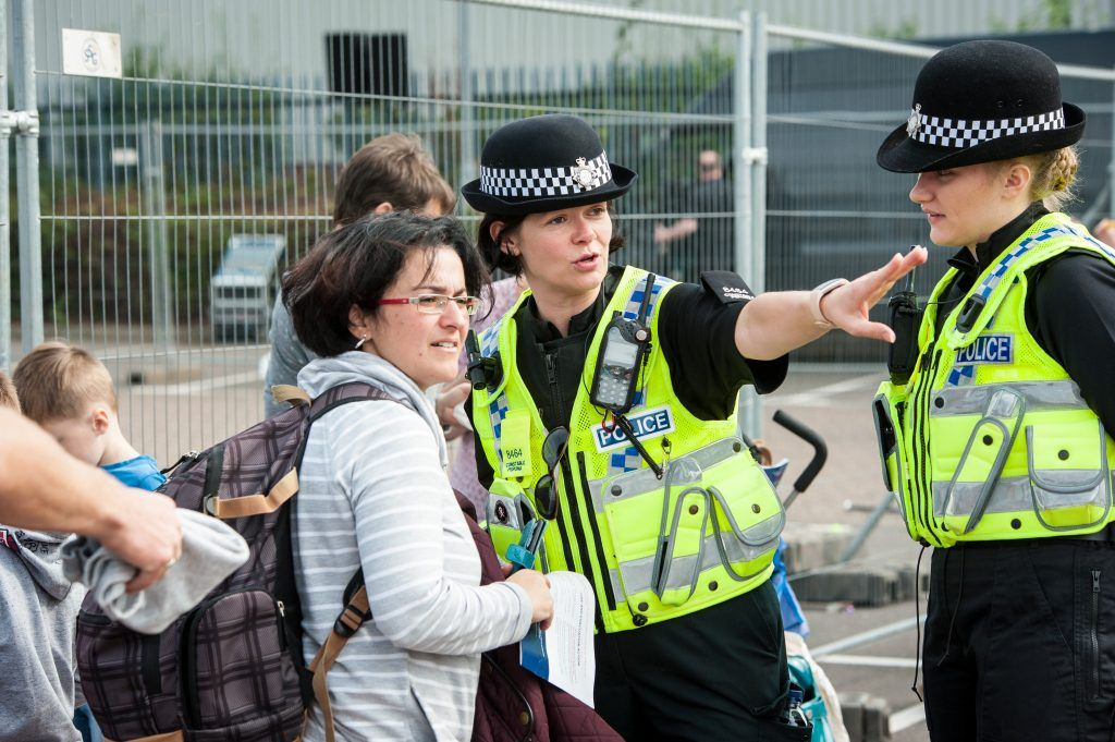 A woman in a stripey hooded jumper and two female police officers with one officer pointing off to the right