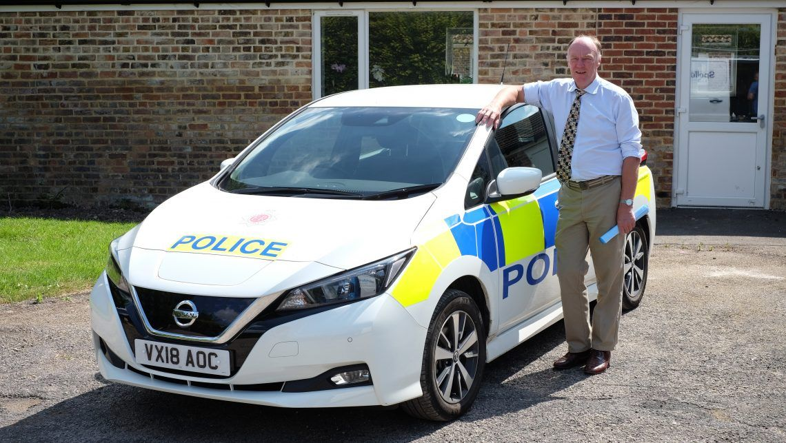 A man in blue shirt, stone chino trousers and colourful tie stands next to a marked electric police vehicle